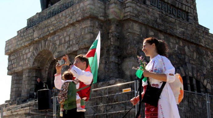 Младо семейство в народни носии качи трите си деца на Шипка